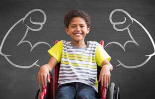 boy in wheelchair in front of muscle arm chalk board